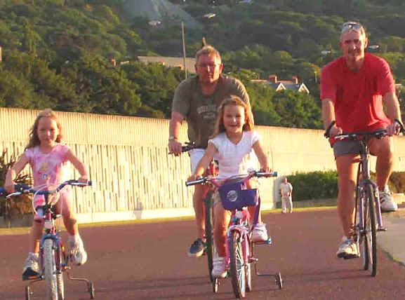 Two men and two small children cycling on Penmaenmawr promenade in evening sunshine