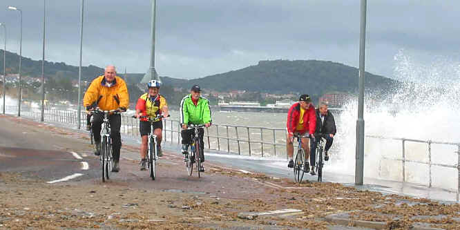 Group cycling on Colwyn prom despite spray from high tide