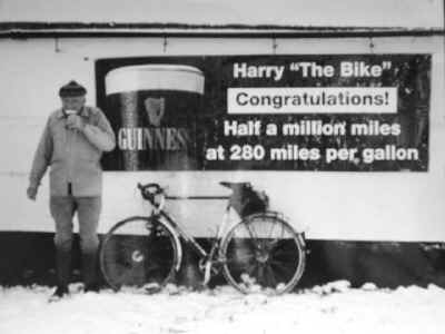 Harry Watson of Deeside drinking a pint of Guinness in front of a Guinness advert congratulating him on cycling half a million miles at 280 miles per gallon