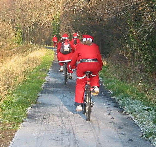 Cycling santas on the cycle path alongside the river Elwy