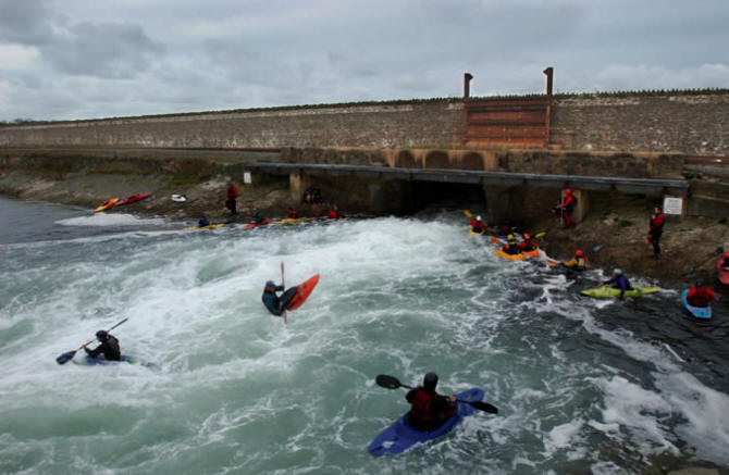 Photo of kayakers tossed about  in turbulent water emerging from the Stanley Embankment flume