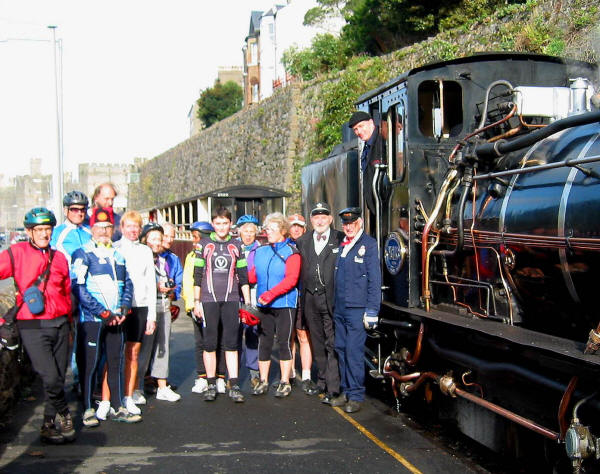 Group of cyclists and staff on platform of Welsh Highland Railway