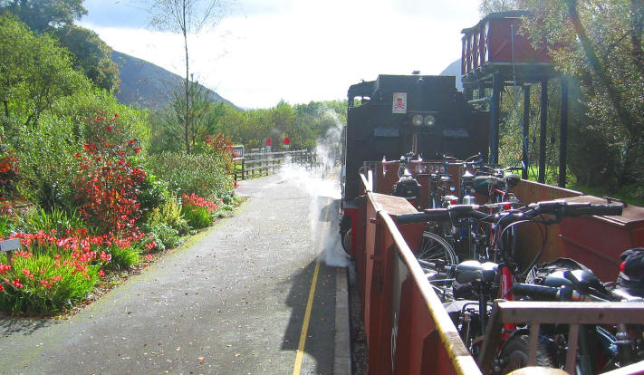 open bike wagon full of bikes immediately behind the Welsh Highland  Railway steam engine stopped at a water tower